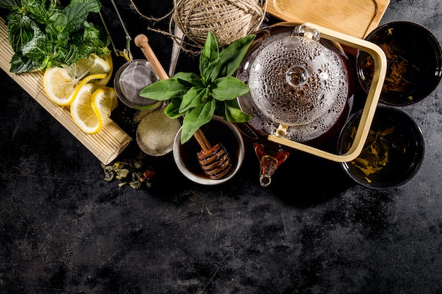 Chá verde fresco saboroso na cerimônia de vidro de bule em fundo escuro acima