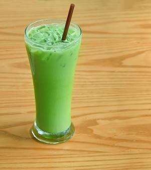 Chá verde frio no chão de madeira.