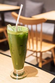 Chá verde gelado contém em um copo alto em forma de v com ambiente de café