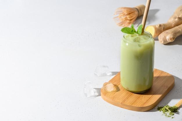 Chá verde gelado do latte do matcha na tabela branca. fechar-se.