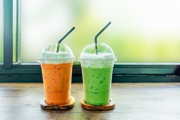 Chá verde gelado e chá gelado tailandês na tabela de madeira.