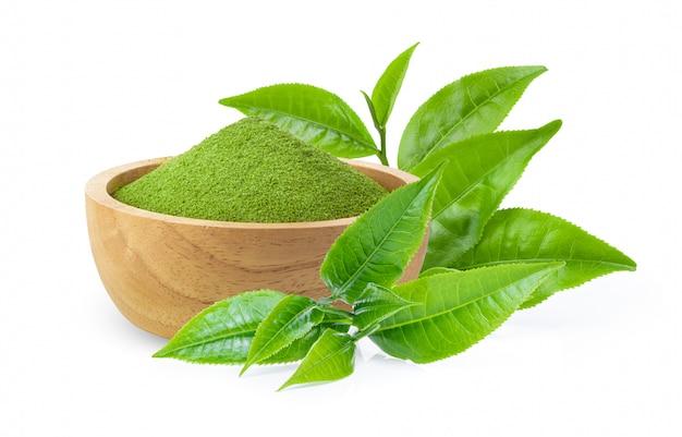 Chá verde instantâneo matcha em uma tigela de madeira com folhas em branco