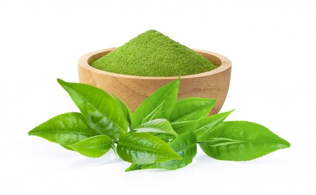Chá verde instantâneo matcha em uma tigela e folhas em branco