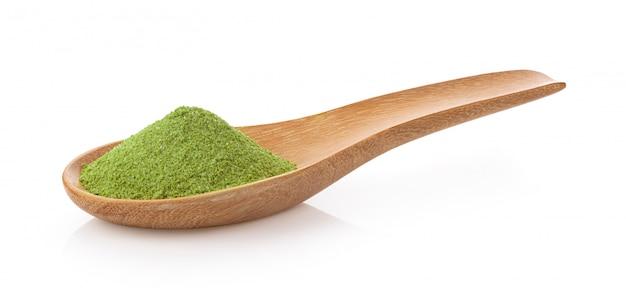 Chá verde instantâneo matcha na colher de madeira em branco