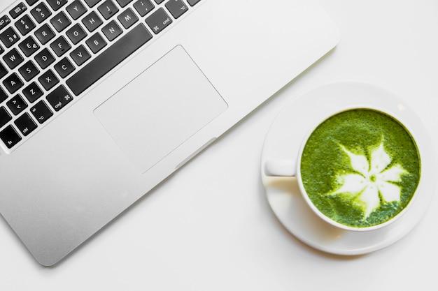 Chá verde japonês com leite em copo branco perto do laptop na mesa branca