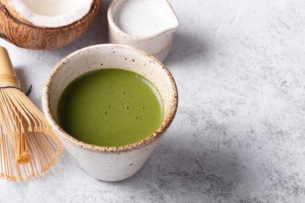 Chá verde japonês matcha com leite no fundo branco.