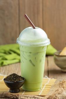 Chá verde, leite gelado e pó matcha no chão de madeira.