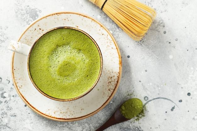 Chá verde matcha com leite em uma xícara com creme sobre um fundo claro de concreto. vista superior com espaço de cópia.