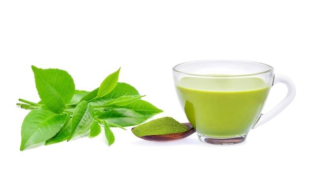 Chá verde matcha com leite quente com chá verde em pó e folhas de chá isoladas no fundo branco.