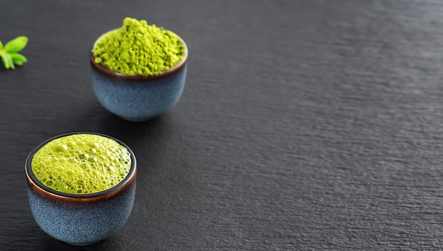 Chá verde matcha em uma tigela de cerâmica azul, ao lado de uma tigela está o chá verde matcha em pó