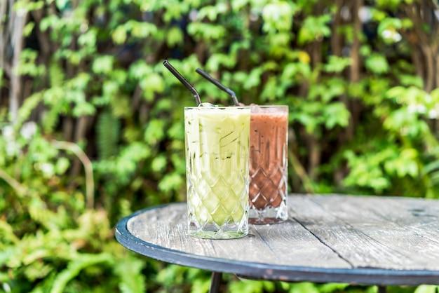 Chá verde matcha gelado e copo de chocolate em cima da mesa