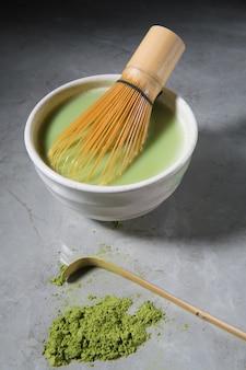 Chá verde matcha latte com chasen de bambu e colher de bambu em uma tigela