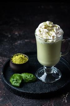 Chá verde matcha latte em um copo de vidro com fundo preto conceito de uma dieta saudável superalimento limpeza antioxidante