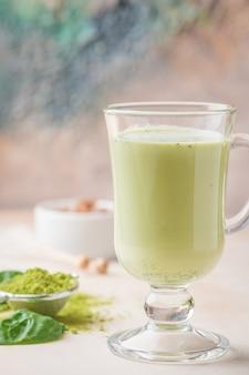 Chá verde matcha latte em um copo de vidro com luz de fundo conceito de uma dieta saudável superalimento limpeza antioxidante