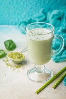 Chá verde matcha latte em um copo de vidro sobre fundo azul conceito de uma dieta saudável superalimento limpeza antioxidante