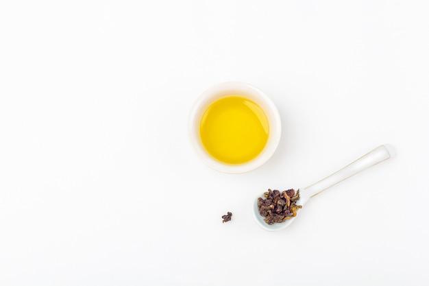 Chá verde no copo cerâmico e chá oolong seco na colher cerâmica em um fundo branco com espaço da cópia para o texto. chá orgânico de ervas, floral e verde asiático para a cerimônia do chá.