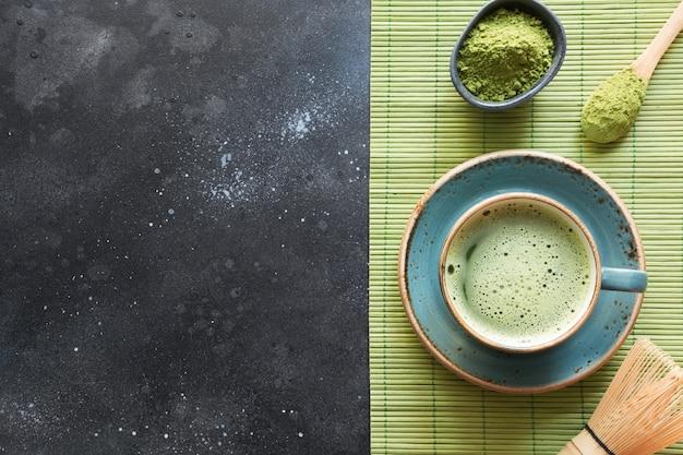 Chá verde orgânico do matcha da cerimônia na tabela preta. vista do topo. espaço para texto.