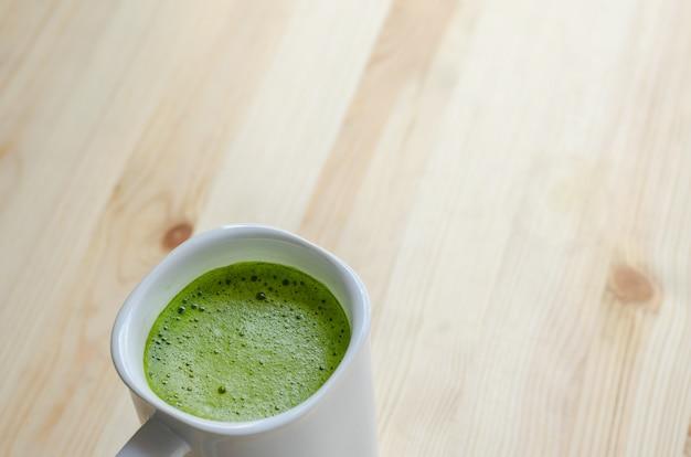 Chá verde quente com leite sobre fundo de madeira