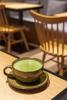 Chá verde quente contém em uma caneca de cor escura com um pequeno prato colocado sobre uma mesa de madeira com ambiente de café