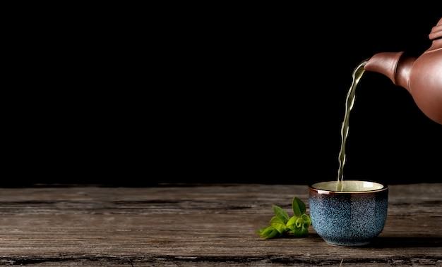 Chá verde quente é derramado do bule de chá na tigela azul