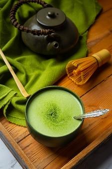 Chá verde quente em um copo com creme coberto com chá verde, decorado com pó de chá verde.