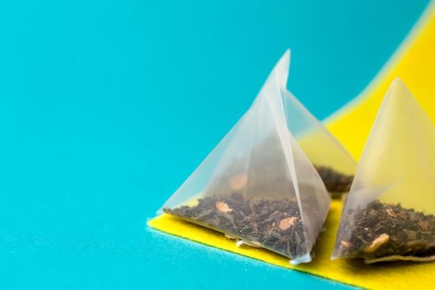 Chá verde saudável em um saco de pirâmide em um fundo azul e amarelo