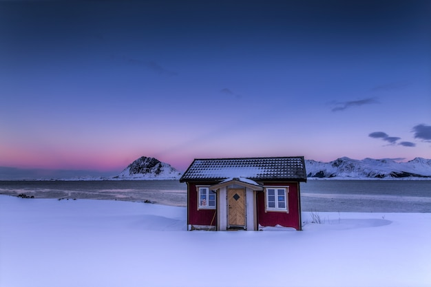 Chalé de madeira no meio de um campo coberto de neve sob o céu colorido da noruega