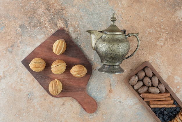 Chaleira antiga e biscoitos redondos doces no fundo de mármore