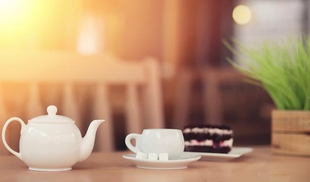 Chaleira com uma bebida e sobremesa no café de rua. chá na xícara de chaleira em cima da mesa. café da manhã com chá e bolos no café.