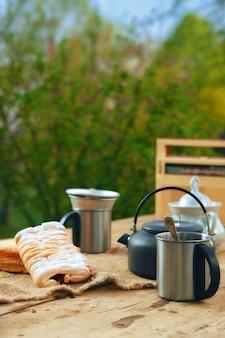 Chaleira de acampamento com uma caneca e biscoito na mesa
