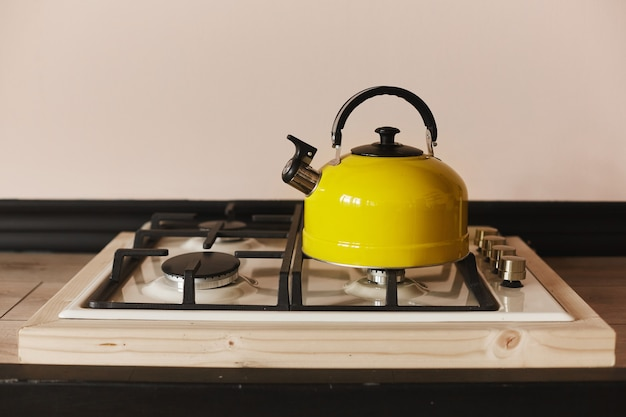 Chaleira de aço amarela no fogão a gás na mesa de madeira. chaleira amarela moderna no fogão a gás de aço inoxidável
