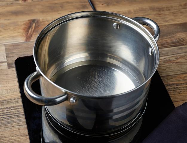 Chaleira de água no fogão elétrico de indução na mesa da cozinha de madeira