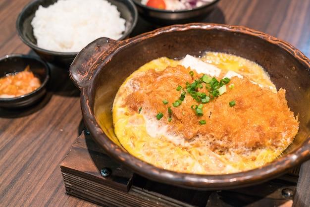 Chaleira de carne de porco fritada em japonês (tonkatsu) coberta com ovo em arroz cozido no vapor.