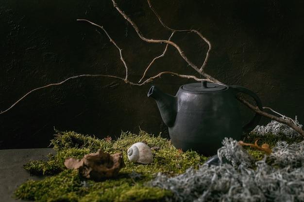 Chaleira de cerâmica artesanal de artesanato em pé sobre musgo com galho seco e folhas. cerimônia do chá de natureza outonal.