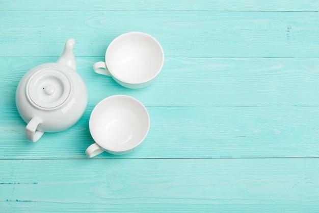 Chaleira de chá cerâmica branca na mesa de madeira fechar
