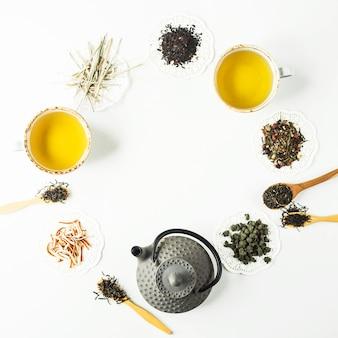 Chaleira de ferro cinza entre diferentes tipos de chá seco, alinhado em um círculo e copos com uma bebida pronta em uma mesa branca