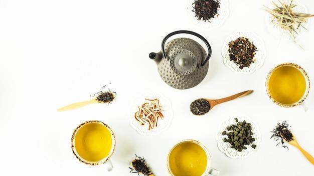 Chaleira de ferro cinza entre diferentes tipos de chá seco