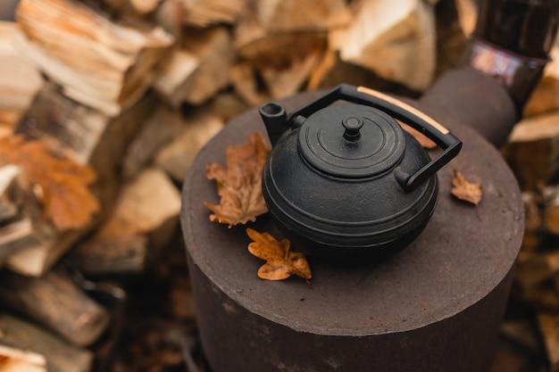 Chaleira de ferro fundido para a tradicional cerimônia oriental do chá no fogão queimado com lindas folhas de carvalho de outono e toras empilhadas no fundo
