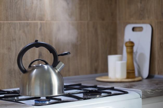 Chaleira de metal prata moderna no fogão a gás e utensílios na cozinha