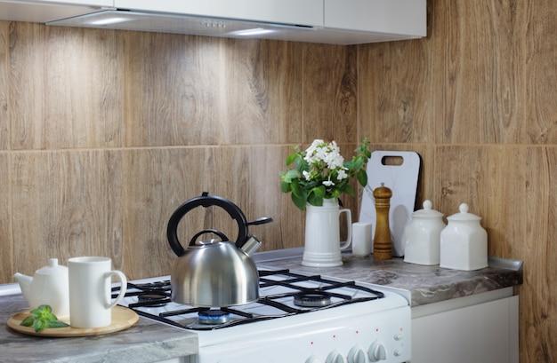 Chaleira de metal prata no fogão a gás e bule com xícara na cozinha