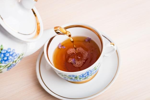 Chaleira de porcelana estilo antigo derramando chá do jarro para a xícara de chá