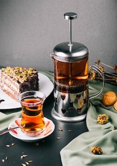 Chaleira de vidro, copo de chá com uma fatia de bolo.