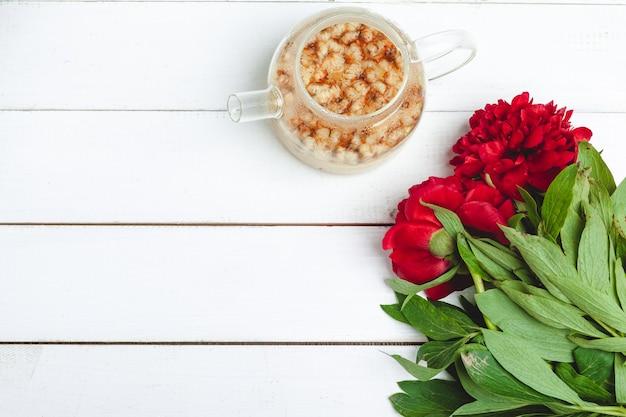 Chaleira de vidro de chá de ervas com flores frescas close-up