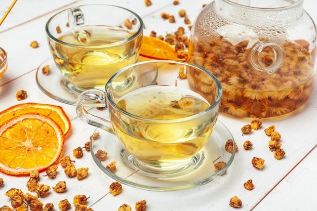 Chaleira de vidro e xícara de chá de ervas no fundo branco de madeira