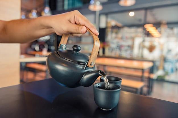 Chaleira derramando água fervente em uma xícara durante o café na cafeteria