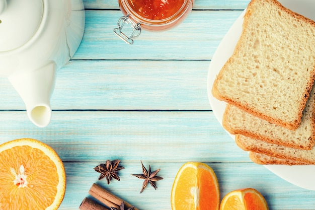 Chaleira, geléia de laranja em frasco de vidro e torradas na mesa de madeira azul, vista superior com espaço de cópia
