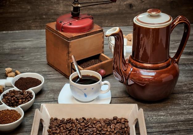 Chaleira velha conceito de cafeína para café, xícaras de café e moedor em um fundo de madeira