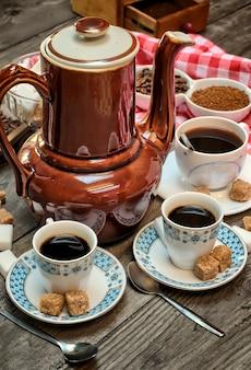 Chaleira velha para café, xícaras de café em um fundo de madeira com um pano vermelho branco