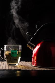 Chaleira vermelha e xícara de chá, ambas saindo da fumaça em uma esteira de madeira