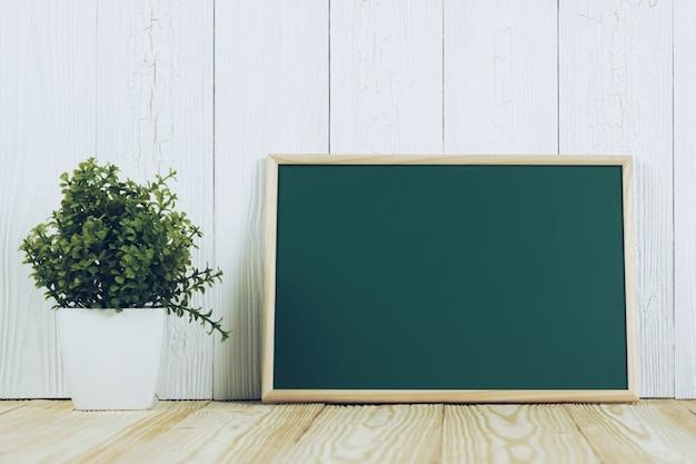 Chalkborad verde em branco com moldura de madeira e pequena árvore na madeira